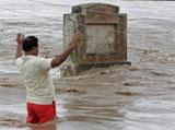 A man tries to balance himself as he attempts to cross floodwaters overflowing a bridge in Kudadarahal village, on Saturday. AP