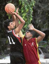 JSC's Gokul (left) goes up for a shot as Surendra of CMP tries to stop him during their clash in the 'A' Division basketball league in Bangalore on Saturday. DH Photo
