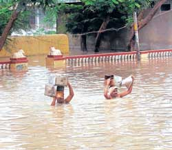 Residents of Kamatagi, Bagalkot district, wade through a flooded street on  Saturday. KPN
