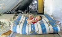 A child lies on a mattress inside a house damaged by an earthquake in Padang Pariaman, a coastal town in the Indonesian province of West Sumatra, on Sunday. REUTERS