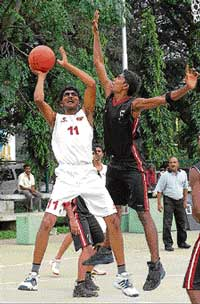 KSP's Ramakrishna (left) goes up for a shot as CMP's Arun Kumar tries to block him during their 'A' Division basketball clash in Bangalore on Sunday . DH Photo