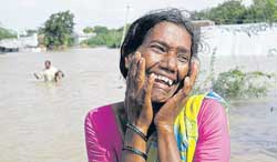 A woman cries after failing to enter her submerged house at Garlapadu village, about 180 km from Hyderabad, on Sunday. AP