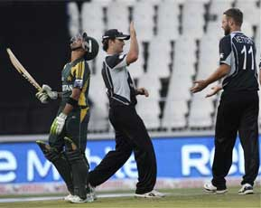 New Zealand captain Daniel Vettori, right, celebrates as Pakistan batsman Umar Akmal, left, is dismissed. AP