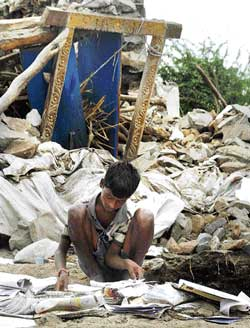 A boy searching for his textbooks in front of his collapsed house in Chintamanadoddi, Sindhanur on Tuesday. DH photo