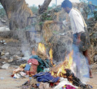 WHAT A WASTE: A resident of Talamari burning old clothes donated for the flood victims. DH PHOTO