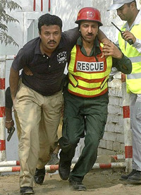 Rescue workers assist a hostage who was released during a crackdown operation against terrorists at a police training school in Lahore on Thursday. AP