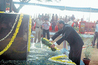 Deputy Commissioner K H Ashwathanarayana Gowda placing a wreath at the martyrs' memorial on Martyrs Day in  Madikeri on Wednesday.  dh photo