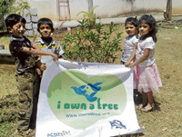 Children pose with a tree at the 'I own a tree' programme organised by the Eco Club at the Jnanabharati campus on World Habitat Day. dh photo