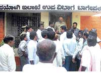 The members of the Road Widening Agitation Committee staging protest after locking up AEE Malleshappa in his office in Bagepalli on Saturday. dh photo