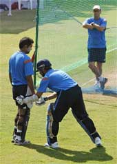 Indian cricketer Sachin Tendulkar, center, helps teammate Gautam Gambhir as coach Gary Kirsten watches during net practice at Vadodara.