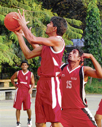 Ajmal (centre) of Ambedkar Basketball Club shoots past Jairaj of Sports Hostel, Bangalore during their 'A' Division clash in Bangalore on Saturday. DH photo