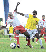 BEL's Pacific (left) and Mahesh of ISRO vie for possession in the Puttaiah Memorial football match. DH PHOTO