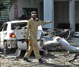 A security official collects evidence at a bomb blast site in Peshawar on Wednesday. AFP