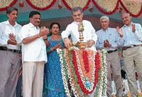 Dharmasthala Dharmadhikari D Veerendra Heggade inaugurating 5,555th Self-Help Group at Cauvery PU College maidan in Gonikoppal on Wednesday. Assembly Deputy Speaker K G Bopaiah, ZP Vice-President Kanjithanda Anitha and others are seen.  DH Photo