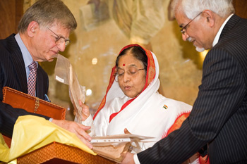 President Pratibha Patil examines a collection of letters written by Mahatma Gandhi as they are presented to her by Sir Gulam Noon (L) and Professor Nat Puri (R) during a ceremony at the Indian High Commission in London on Wednesday. AFP