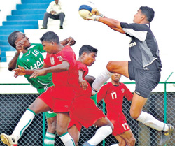 MEG goalkeeper Malay Paul thwarts an attempt by HASC's Fredrick (left) during their clash in the Puttaiah Memorial Football tournament in Bangalore on Thursday. DH Photo