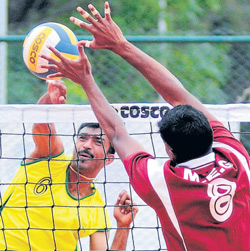 SWR's Cristy smashes against a block from MEG's Jince in their State 'A' Division volleyball tournament match in Bangalore on Thursday. DH Photo