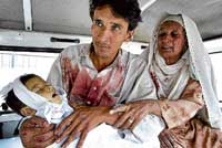 A man holds his baby girl who was killed in a suicide bombing, as her grandmother mourns inside a van at a local hospital in Peshawar on Sunday. AP