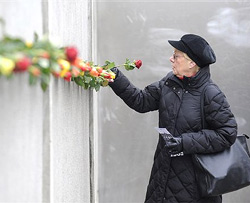 A woman places a rose into part of the former Berlin wall during a commemoration ceremony to mark the 20th anniversary of the fall of the Berlin Wall, in Berlin on Monday. AP