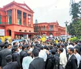 Under siege: Agitating advocates gather outside the High Court in protest against Chief Justice P D Dinakaran in Bangalore on Monday. DH photo