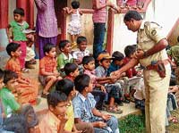 Police team led by Circle Inspector D T Prabhu distributing sweets to school and college students as part of the Children's Day on Saturday. dh photo