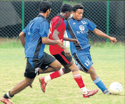 New Horizon's Ranjit (right) looks to clear as Karnataka Vidyashala's Gilbert (centre) looks on in their inter-collegiate football clash on Tuesday. DH photo