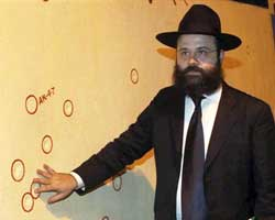 Rabbi Avraham Berkowitz, Director of the Chabad Mumbai Relief Fund, showing bullet marks on a wall right opposite Nariman House during a multi-faith candle light vigil in the memory of 26/11 terror attacks victims in Mumbai on Tuesday. Nariman House is the Jewish center where the terrorists killed a rabbi, his wife and a National Security Guard commando in 2008. PTI