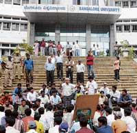 Students staging a protest in Bangalore University on Wednesday, demanding facilities in the hostel. dh photo