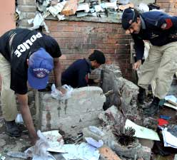 Pakistani police officials examine the site of the suicide bomb blast in Peshawar on Thursday. AFP