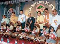 Tiny tots of Canara School temporarily occupying the chairs for dignitaries prior to the inauguration of Canara School in Mangalore on Thursday. dh photo