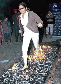A corporate employee walks over embers during a workshop in Amritsar on Thursday night. PTI