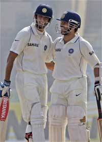 Indian cricketer Rahul Dravid, left, is congratulated by teammate Sachin Tendulkar for scoring a century on the second day of the second cricket test match between India and Sri Lanka in Kanpur, India, Wednesday.AP
