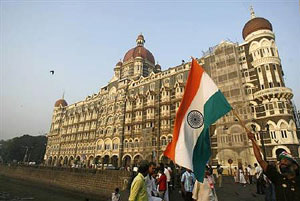 A man walks with the Indian national flag in front of the Taj Mahal hotel, one of the sites of last year's terror attacks, in Mumbai on Thursday. Reuters
