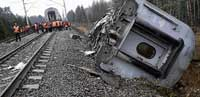 Deadly tracks: Railroad workers stand next to a damaged coach at the site of a train derailment near the town of Uglovka, some 400 km north-east of Moscow, Russia, on Saturday. AP
