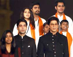 Bollywood actor Shahrukh Khan and Olympic gold medalist Abhinav Bindra sing the national anthem at a programme on the first anniversary of the final day of the seige of 26/11 in Mumbai, in New Delhi on Sunday. PTI