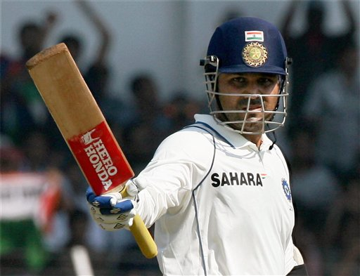Virendra Sehwag raises his bat after scoring a double century.PTI