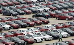 In this Oct. 30, 2009 file photo, a man walks through a parking lot occupied by Chevrolet Cruze models at a local joint manufacturer with Shanghai GM in Shengyang, in northeast China's Liaoning province. AP