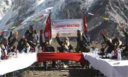 Nepal's Prime Minister Madhav Kumar Nepal, center, and members of the cabinet raise hands in favor of a document to highlight the negative impacts of global warming on Mount Everest, seen in the background, during a special cabinet meeting at Kalapatthar in Nepal, Friday. AP