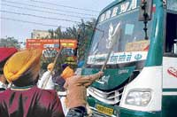 Sikh protesters damage buses after police stopped a religious programme in Ludhiana on Saturday. PTI