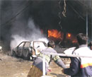 Vehicles are seen on fire after a blast in Peshawar market on Saturday. AP