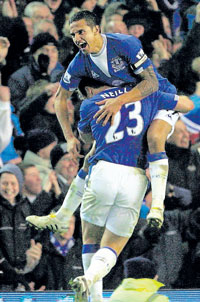 Everton's Tim  Cahill celebrates with team-mate Lucas Neill after scoring  the equaliser in their draw against Tottenham Hotspur on Sunday. AFP