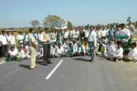 The members of the Rajya Raitha Sangh and Hasiru Sene staging a protest on the four-lane bypass road on NH 7 on the outskirts of Chikkaballapur. The members demanded service roads on either sides of the bypass road. dh photo