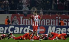 Olympiakos' players celebrate their qualification to the next round of Champions League after the end of a group H soccer match against Arsenal at the Karaiskakis stadium in the port of Piraeus, near Athens, on Wednesday. AP