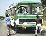 A bus being damaged by men protesting against the seperation of Telangana from Andhra Pradesh in Ralyalseema on Thursday. PTI