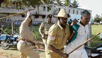 Police caning a farmer in Chamarajnagar on Friday. dh Photo