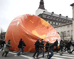Protestors run off with a balloon representing the volume of one metric ton of carbon dioxide during a demonstration in Copenhagen on Monday. AP