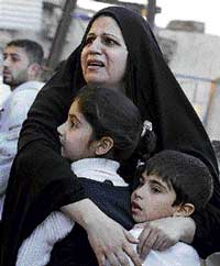 An Iraqi women hugs her children at the site of a car bomb attack in Baghdad, Iraq, on Tuesday. AP