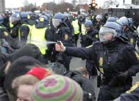 A Danish riot police officer uses pepper spray, as police push back protestors during a demonstration outside the Bella Center in Copenhagen. AP