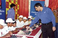 MASTER AT WORK: Viswanathan Anand takes on school children in Bangalore on Saturday.