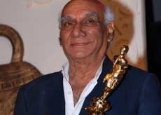 Indian Bollywood producer and director Yash Chopra holds his trophy during the V Shantaram Awards 2009 ceremony in Mumbai on Monday. AFP